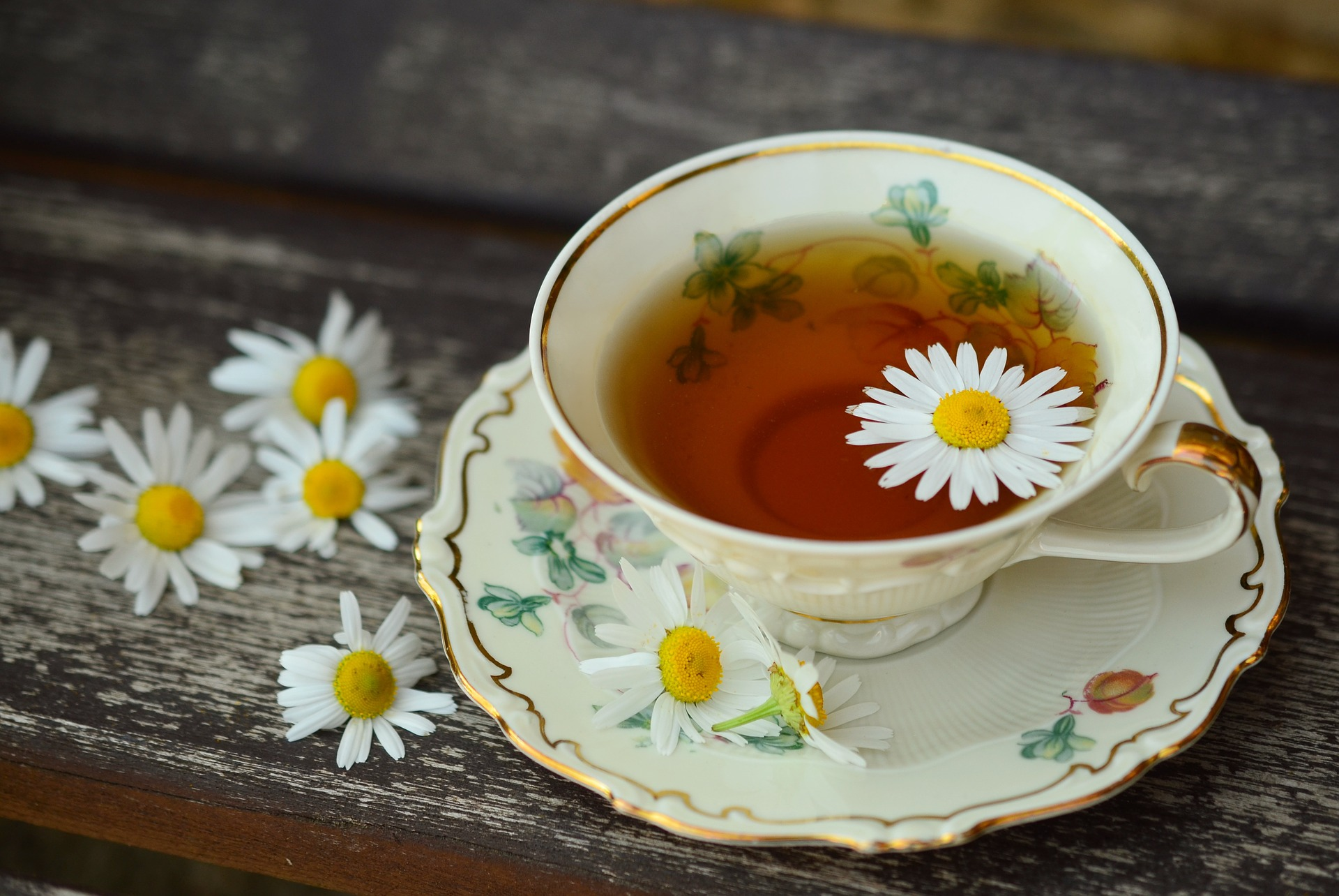 daisies and cup of tea on rustic table