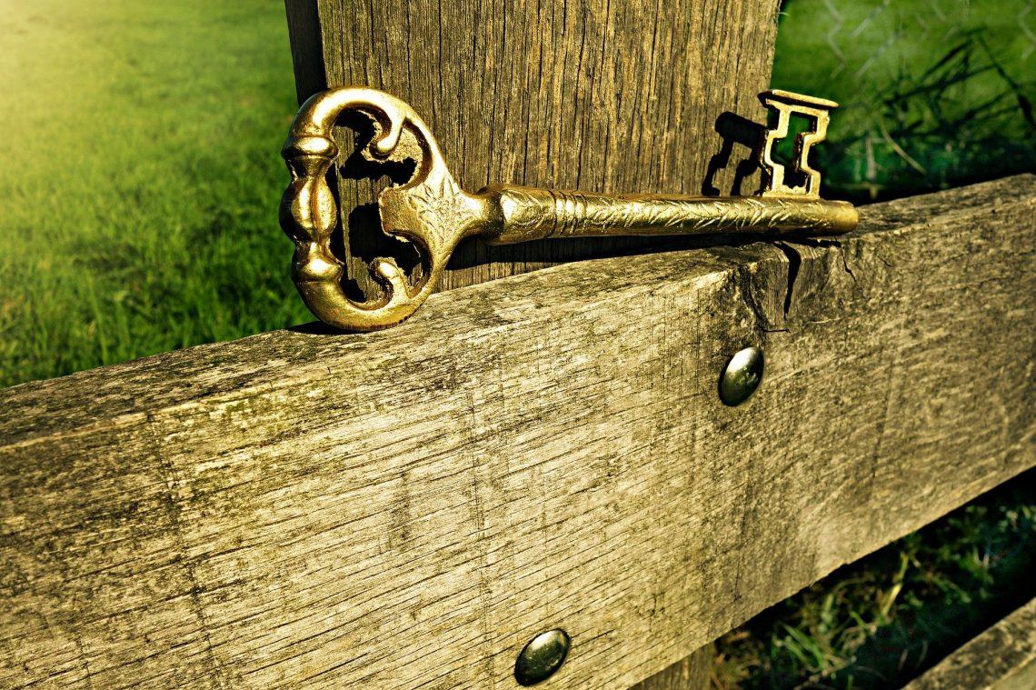 skeleton key; weathered wood fence; rustic