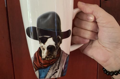 western dog mug with cowboy hat, vest, bandana, and eye patch in front of a wooden barn door