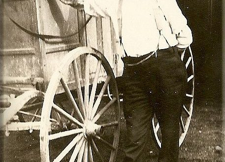mail carrier from 1800s standing in front of mail carriage